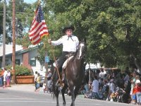 Sheriff's posse carrying a flag while riding a horse
